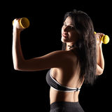 Portrait of a young brunette sporty fitness woman with dumbbell Royalty Free Stock Photography