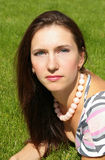 Portrait of a young brunette woman. Portrait of a young beautiful woman on the green grass background Stock Photos