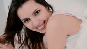 Portrait of young brunette woman in the bed. Beautiful girl hiding under the sheet, smiling at camera. Royalty Free Stock Photography