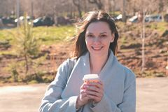 Portrait of young brunette woman in coat walks in city park and drinks coffee. Springtime. royalty free stock photography