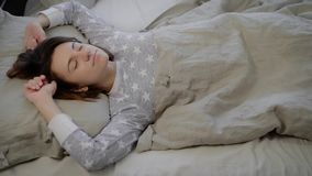 Portrait of young brunette woman dressed in grey pyjamas lying and sleeping in bed covered with linen at home. Beautiful