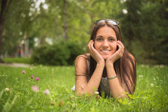 Portrait of a young brunette  woman enjoying the lying on the gr Royalty Free Stock Photo