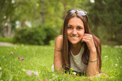 Portrait of a young brunette  woman enjoying the lying on the gr Stock Photography