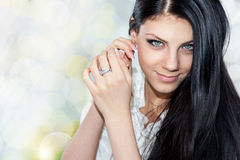 Portrait of young brunette woman fixing earring Royalty Free Stock Image