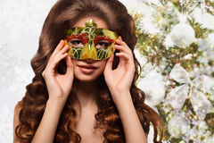 Portrait of young brunette woman in a gold mask on a gold winter background. Portrait of young brunette woman in a gold carnival mask on a  magic winter Royalty Free Stock Photography