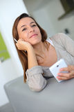 Portrait of young brunette woman holding smartphone Royalty Free Stock Photo