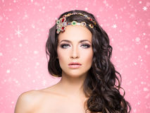 Portrait of a young brunette woman in jewelry. Beautiful brunette with luxury golden necklace over pink winter background. Christmas concept Royalty Free Stock Photos