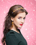Portrait of a young brunette woman in jewelry. Beautiful brunette with luxury golden necklace over red winter background. Christmas concept Stock Image