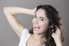 Portrait of a young brunette woman making faces with different e Royalty Free Stock Photography