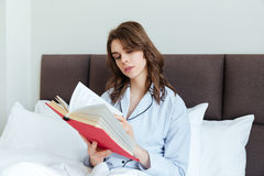 Portrait of a young brunette woman in pajamas reading book Stock Photos