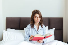 Portrait of a young brunette woman in pajamas reading book Royalty Free Stock Images