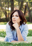 Portrait of a young brunette woman in the park royalty free stock photography