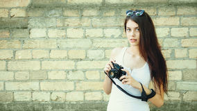 Portrait of a young brunette woman posing with a film camera in a brick wall background Stock Photos