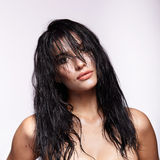 Portrait of a young brunette woman with shining wet make-up and Stock Images