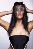 Portrait of a young brunette woman with shining wet make-up and Royalty Free Stock Images