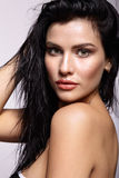 Portrait of a young brunette woman with shining wet make-up and Royalty Free Stock Image