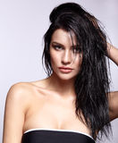 Portrait of a young brunette woman with shining wet make-up and Stock Photo