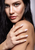 Portrait of a young brunette woman with shining wet make-up and Stock Photography
