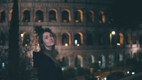 Portrait of young brunette woman standing near Colosseum in Rome, Italy in evening. Girl turns and looks at camera. Hair waves in the wind. Female exploring Royalty Free Stock Photography