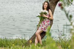 Portrait of a young brunette woman. In a summer dress in flower Royalty Free Stock Photos