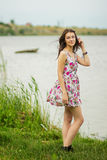 Portrait of a young brunette woman. In a summer dress in flower Stock Photos