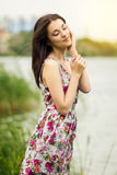 Portrait of a young brunette woman. In a summer dress in flower Royalty Free Stock Photography