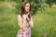 Portrait of a young brunette woman. In a summer dress in flower Royalty Free Stock Images