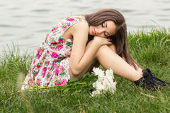Portrait of a young brunette woman. In a summer dress in flower Stock Image