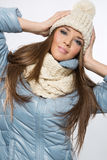 Portrait of a young brunette woman wearing a wool beige cap and. Scarf and blue jacket stock photo