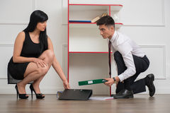 Portrait of young business couple flirting near. The office cabinet at workplace while picking some folders on the floor and looking to each other, relationship Stock Photo