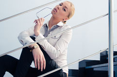 Portrait of young business fashion woman holding glasses & sitting on stairs Stock Image