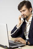 Portrait of young business man communicating. On telephone while using computer Stock Image