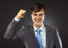 Portrait of a young business man enjoying success. Against a gray background Stock Image