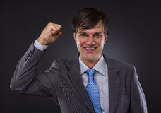 Portrait of a young business man enjoying success. Against a gray background Stock Images