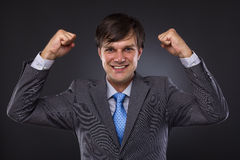 Portrait of a young business man enjoying success. Against a gray background Royalty Free Stock Images