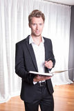 Portrait young business man in suit taking notes into book Royalty Free Stock Photography