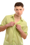 Portrait of a young business man taking off his green shirt. Man doing striptease. Stock Images