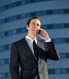 Portrait of a young business man talking on cellphone outdoors. Close up portrait of a young business man talking on cellphone outdoors Royalty Free Stock Photography