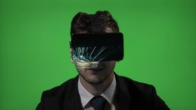 Portrait of a young business man using futuristic reality headset to test the launching of a new game at work on green screen -. Portrait of a young business man stock video