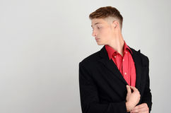 Portrait of a young business man wearing a suit and a red shirt looking over the shoulder. Stock Photography