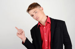 Portrait of a young business man wearing a suit and a red shirt pointing to the side. Royalty Free Stock Image