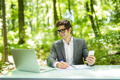 Portrait of young handsome business man working at laptop at office table and talk at phone with costumer and make notice in green. Portrait of young business stock images