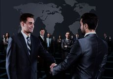 Portrait of young business people. Handshake in front of business people. Portrait of young business people. Handshake in front of business people Stock Photos
