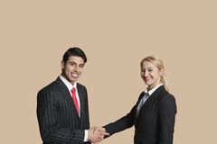 Portrait of young business people shaking hands over colored background Stock Photo