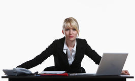 Portrait of the young business woman. Sitting at a desktop Stock Image