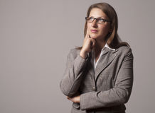 Portrait of young business woman in the glasses. Portrait of a young successful woman, looks up and thinks Stock Images