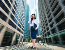 Business woman, bottom view, blur skyscapers. Portrait of young business woman in glasses and white blouse with notebook in hand, bottom view, blur skyscapers on Royalty Free Stock Photos