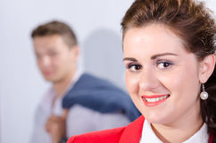 Portrait of young business woman with her colleague at the back Royalty Free Stock Photos