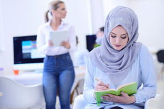 Portrait of young business woman at modern startup office interior, team in meeting in background Stock Photography