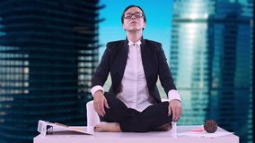 Portrait of young business woman in the office. She sat on the Desk in the Lotus position and meditating in a business stock footage